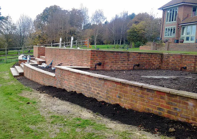 A side on view of the curved retaining walls with sandstone cappings.