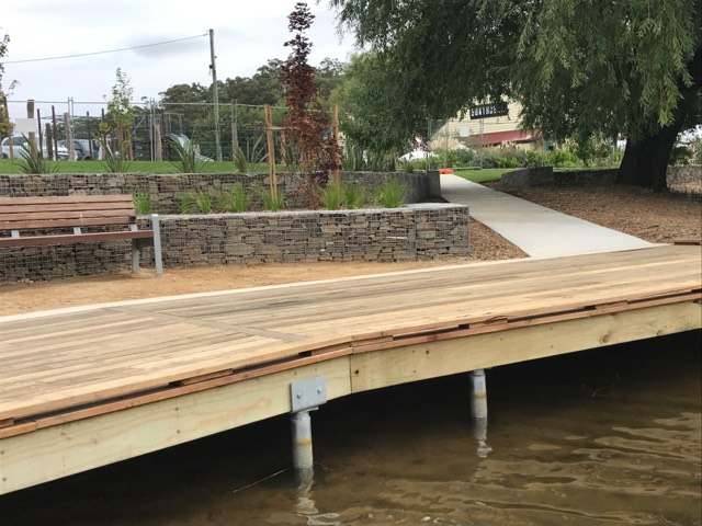 Decking surrounds the water edge leading away to the cafe