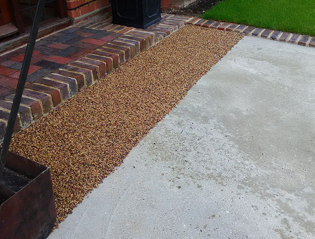 Finished edged and concreted drive. Spreading Resin Bound Toffee Aggregate before hand trowelling