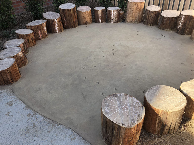 The finished coloured concrete circle with bird footprints and log seating.